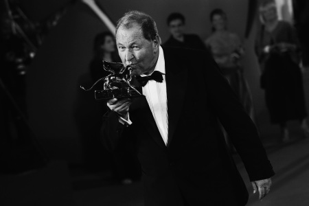 Director Roy Andersson poses with the Golden Lion Award for Best Film for 'A Pigeon Sat On A Branch Reflecting On Existence' during the award winners photocall of the 71st Venice Film Festival