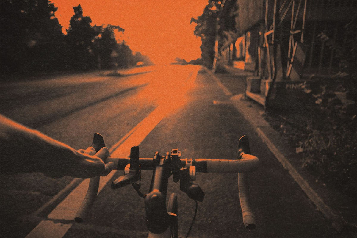 A hand holding the handlebars of a bicycle in a bike lane