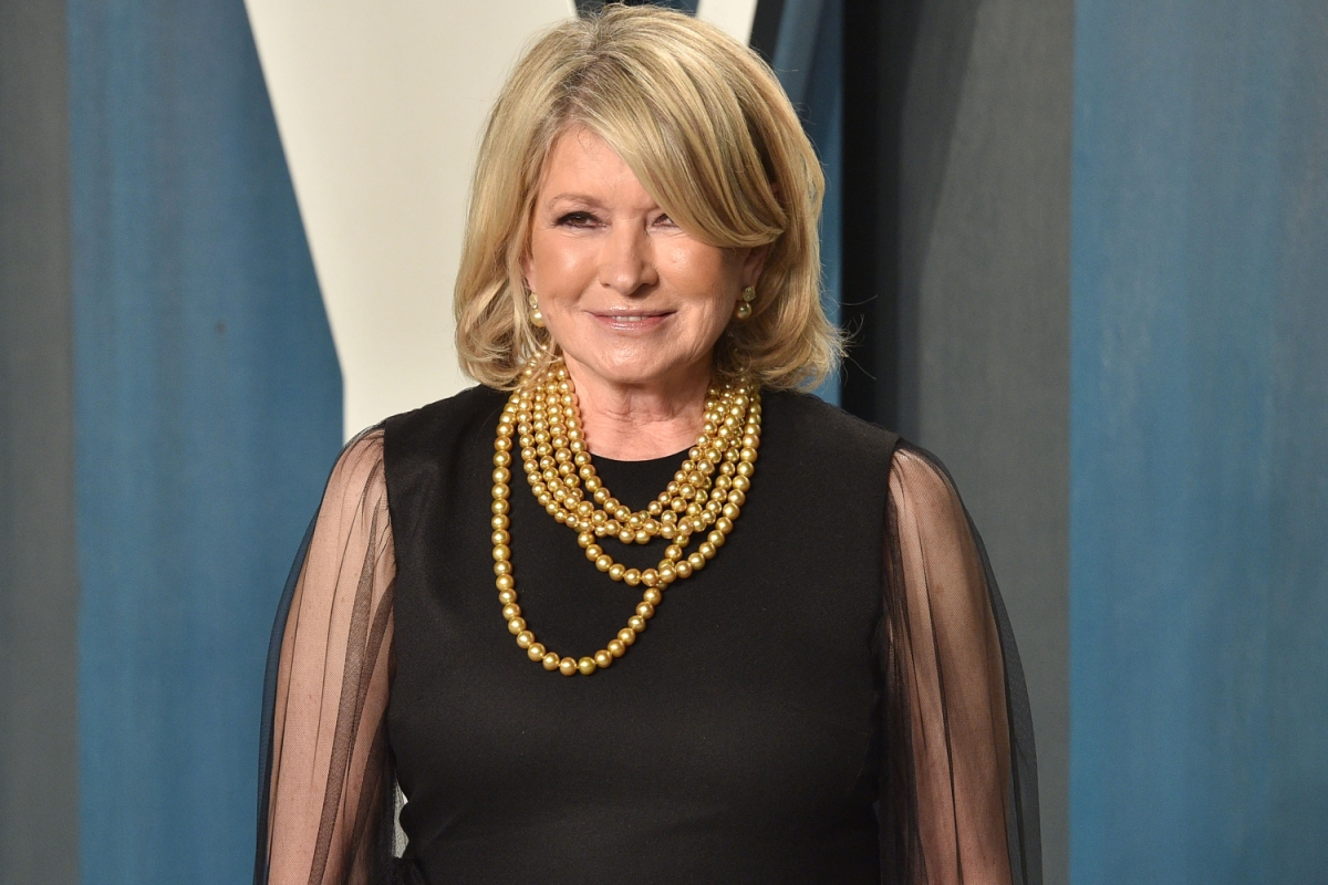 Martha Stewart poses in a black dress and gold necklace