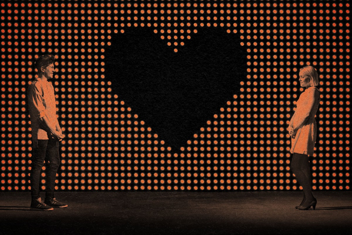 Two people stand far apart from each other on either side of a giant black heart background