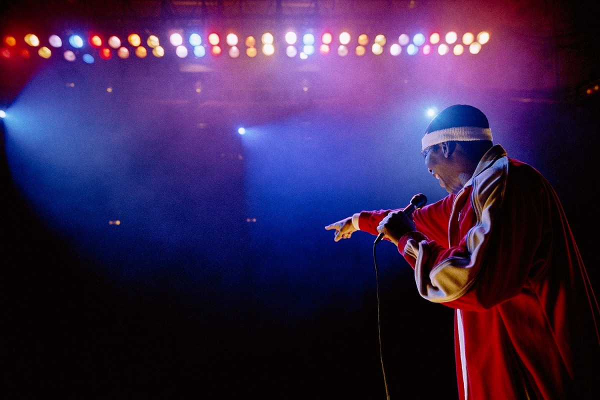 Rapper on stage under blue and purple stage lights, pointing out at audience