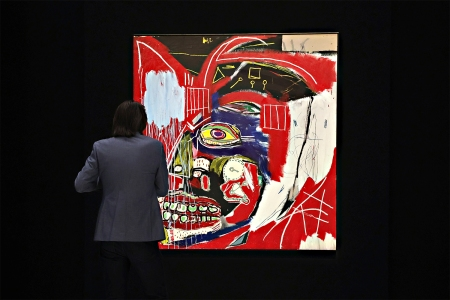 """A person standing in front of """"In This Case,"""" a painting by Jean-Michel Basquiat"""