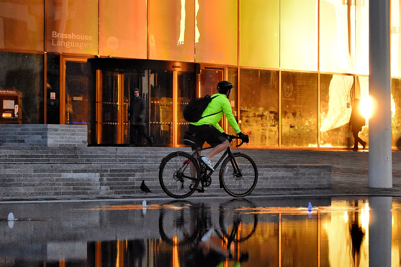 A bike commuter in a fluorescent green jacket biking at sunrise