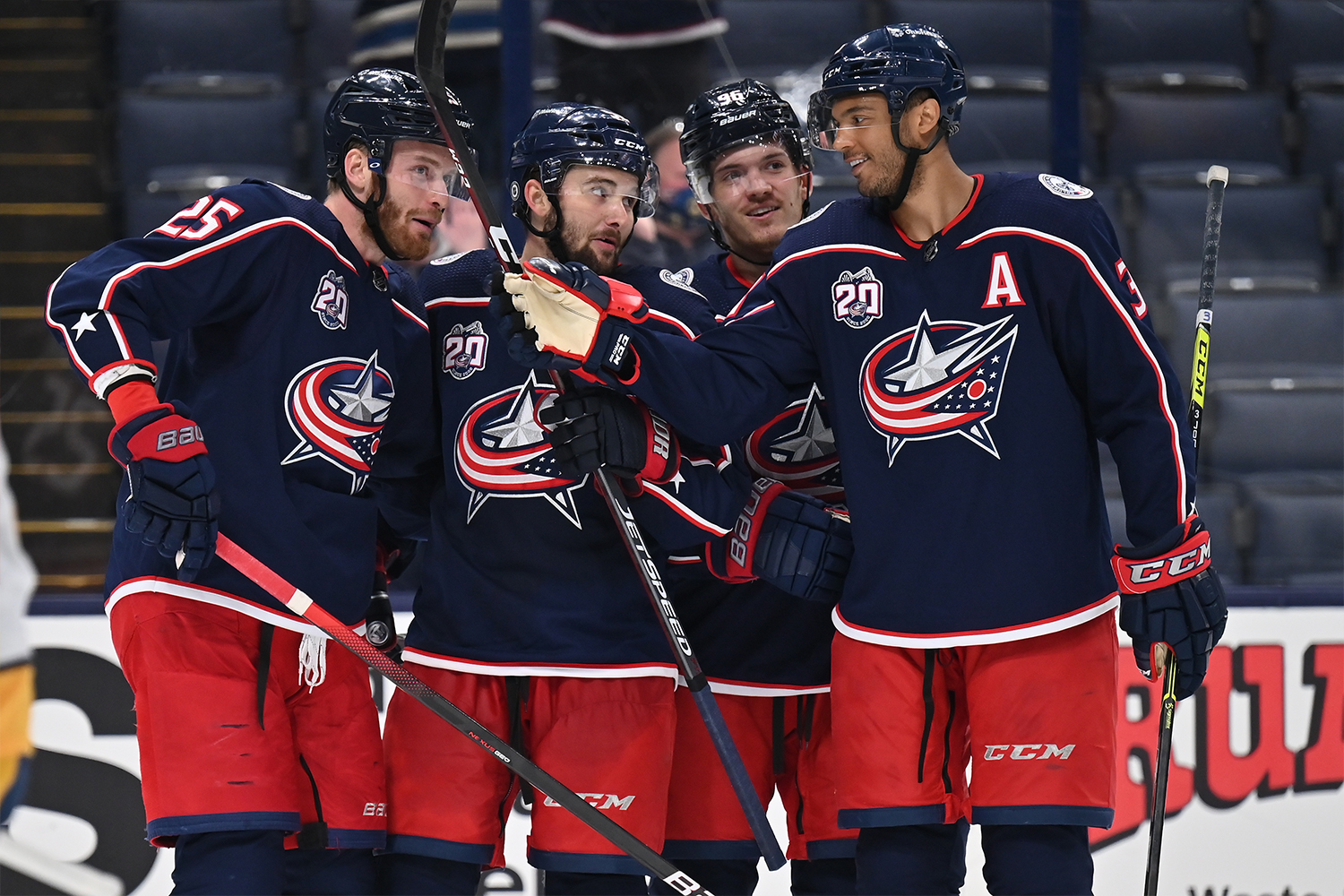Mikhail Grigorenko #25, far left, Emil Bemstrom #52, Jack Roslovic #96 and Seth Jones #3, all of the Columbus Blue Jackets celebrate Bemstrom's second goal of the third period against the Nashville Predators at Nationwide Arena on May 3, 2021