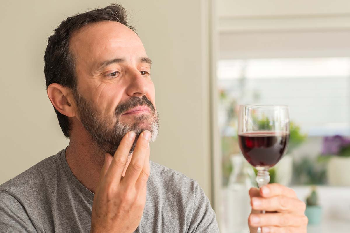 A middle age man drinking a glass of wine serious face thinking about question, very confused idea