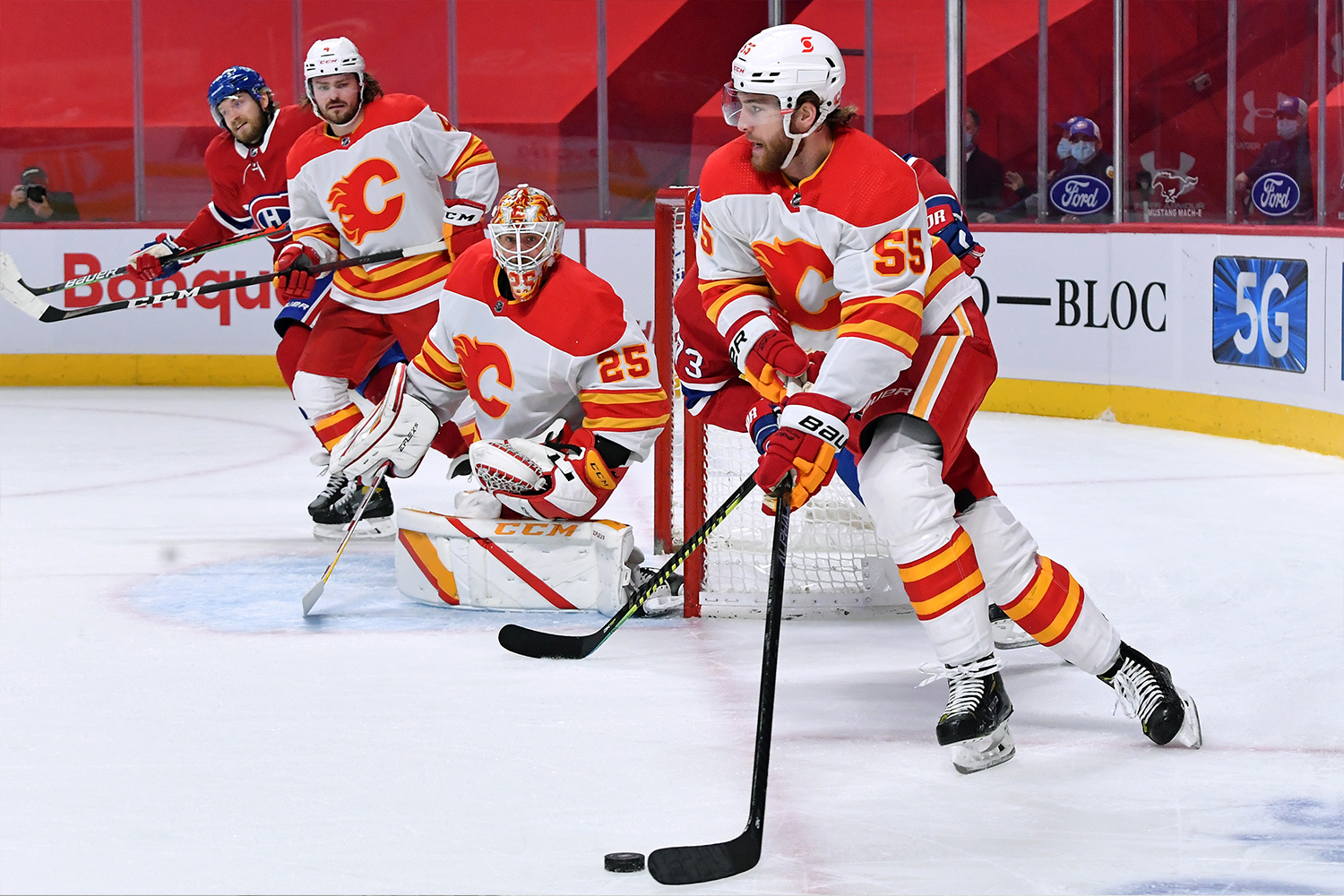 Noah Hanifin #55 of the Calgary Flames looks to pass the puck against against the Montreal Canadiens in the NHL game at the Bell Centre on April 16, 2021