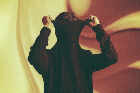 Man pulling turtle neck sweater over his face