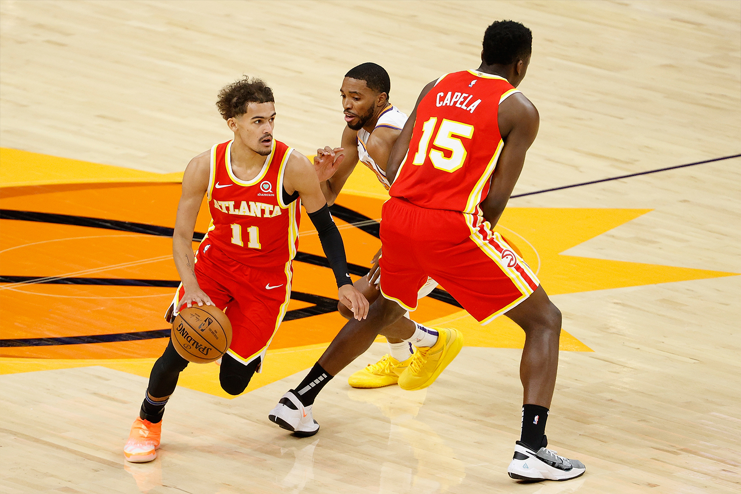 Trae Young #11 of the Atlanta Hawks moves the ball past Mikal Bridges #25 of the Phoenix Suns