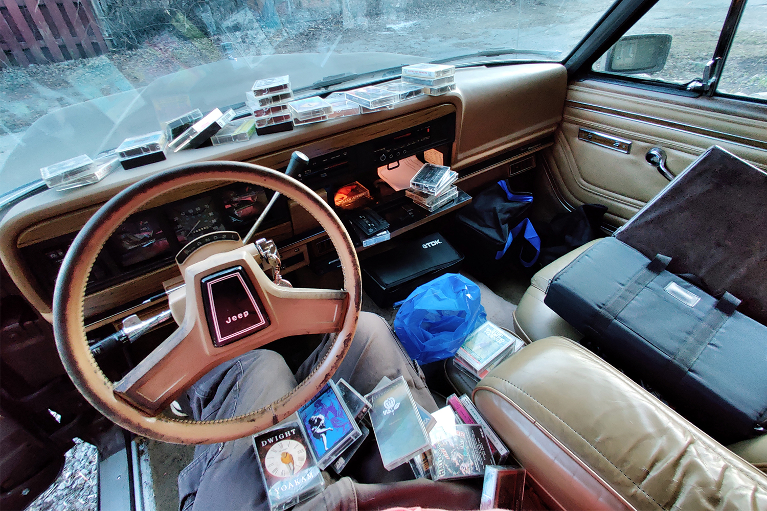 The front two seats of a 1987 Jeep Grand Wagoneer with a bunch of cassette tapes