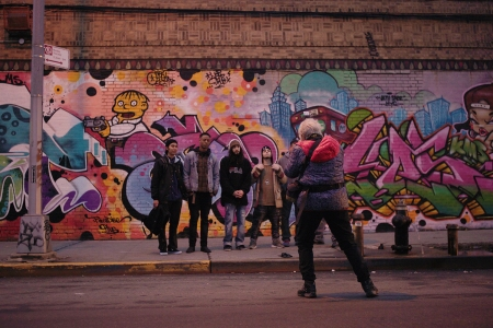 Martha Cooper shooting in front of a mural