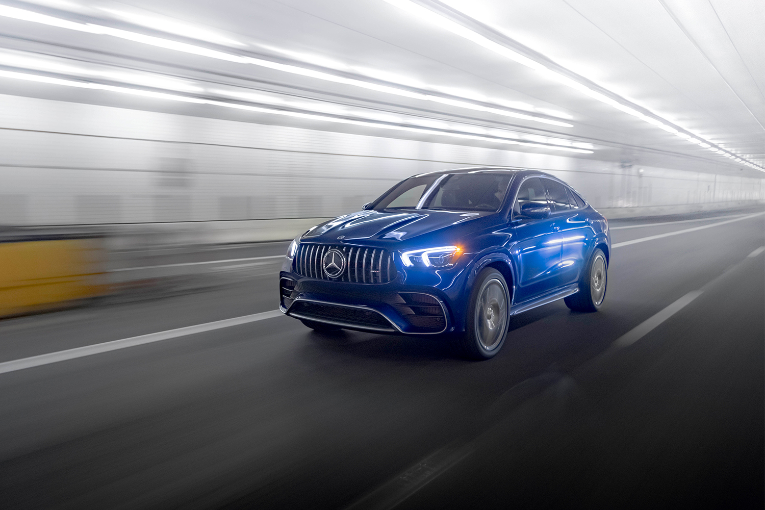 A blue Mercedes-AMG GLE 63 S Coupe driving through a lit tunnel