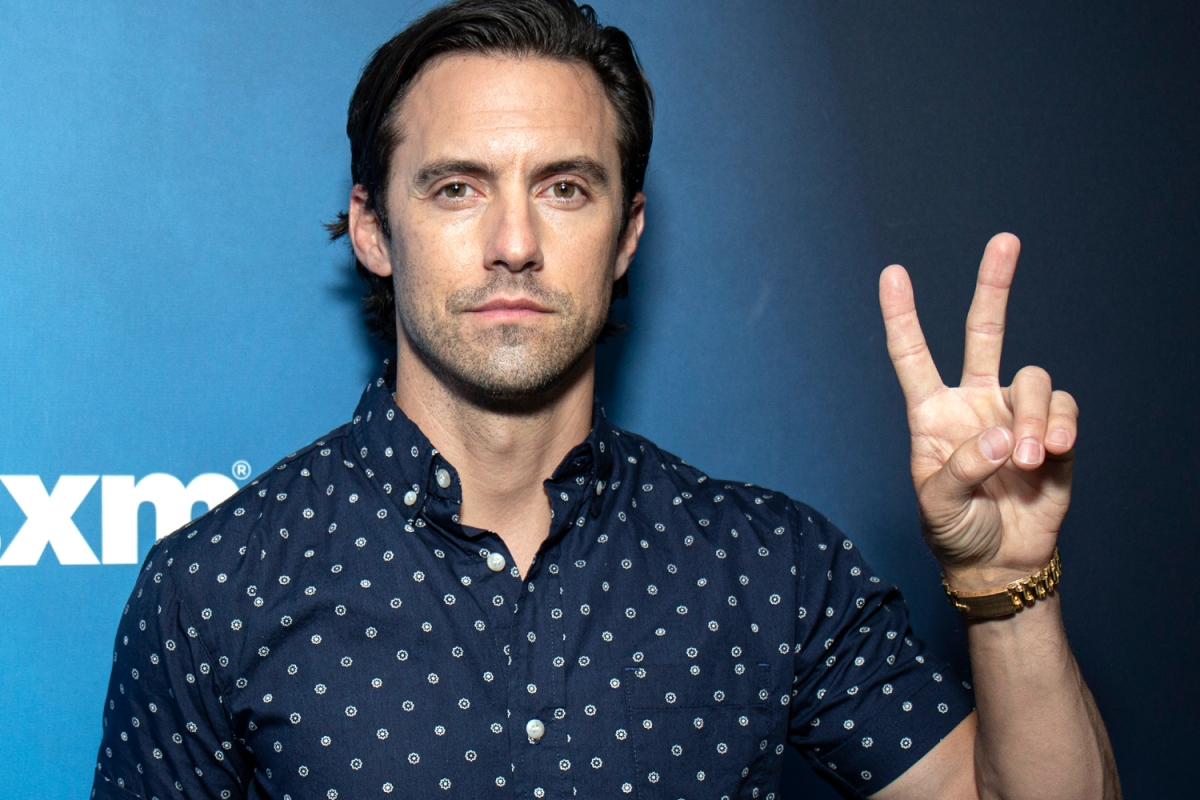 Milo Ventimiglia throws up a peace sign while posing against a blue backdrop