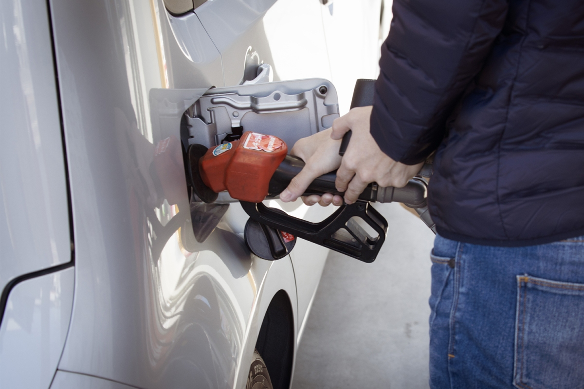 A person pumping gas into a vehicle at a gas station