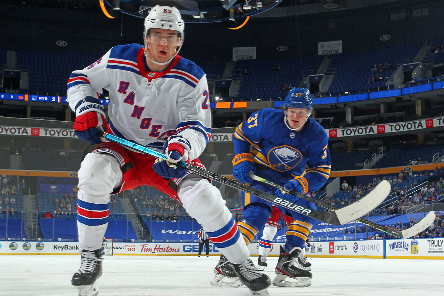 Libor Hajek #25 of the New York Rangers and Casey Mittelstadt #37 of the Buffalo Sabres follow the puck during an NHL game on April 3, 2021