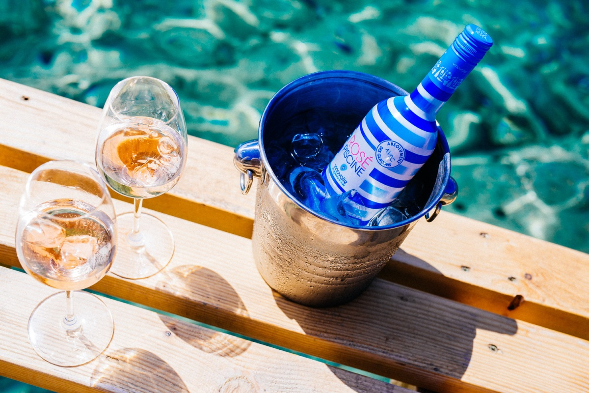 Blue and white striped bottle of Rosé Piscine in an ice bucket, next to two glasses of rosé, by blue-green water