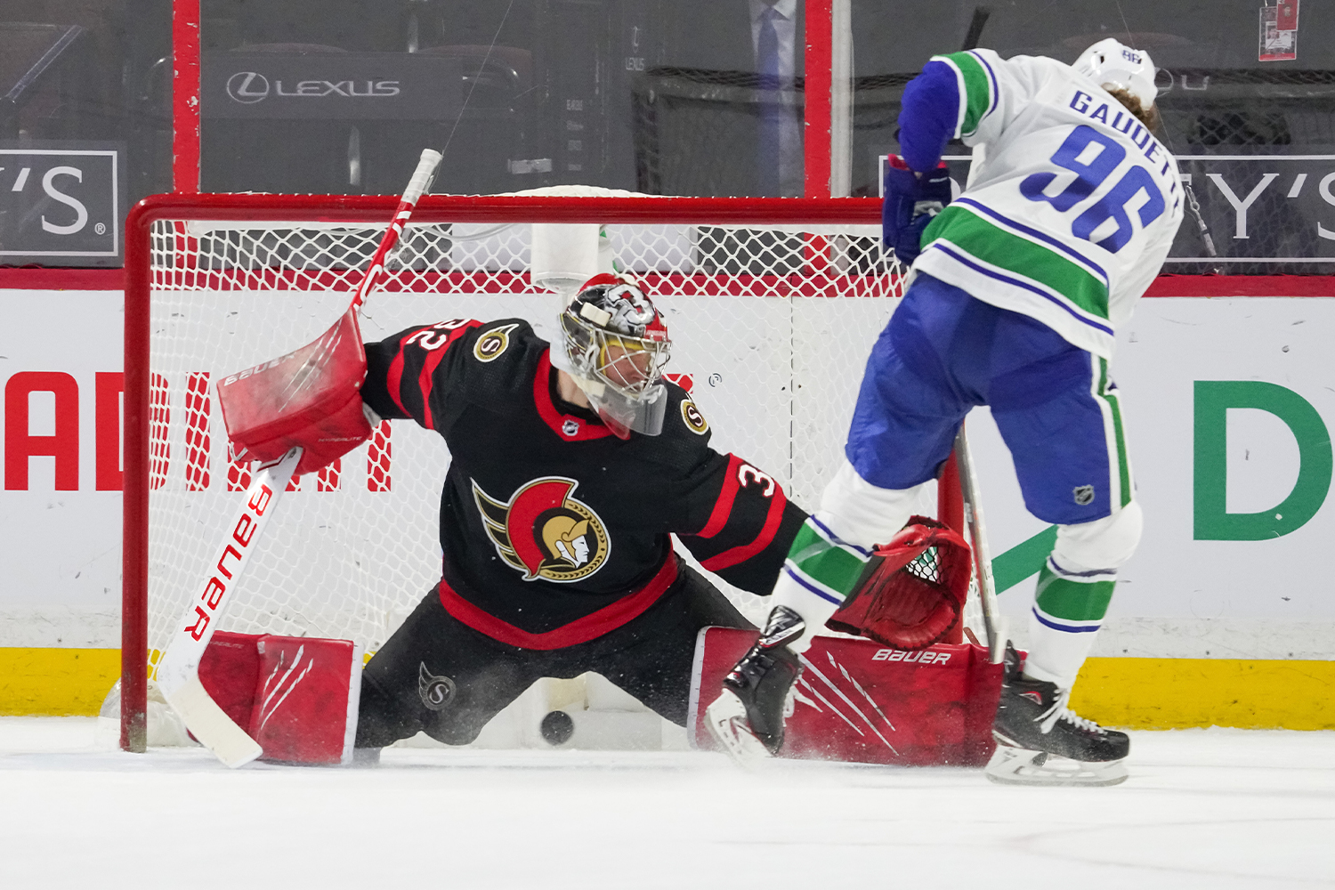 Adam Gaudette #96 of the Vancouver Canucks scores the shootout winning goal against Filip Gustavsson #32 of the Ottawa Senators at Canadian Tire Centre on March 17, 2021