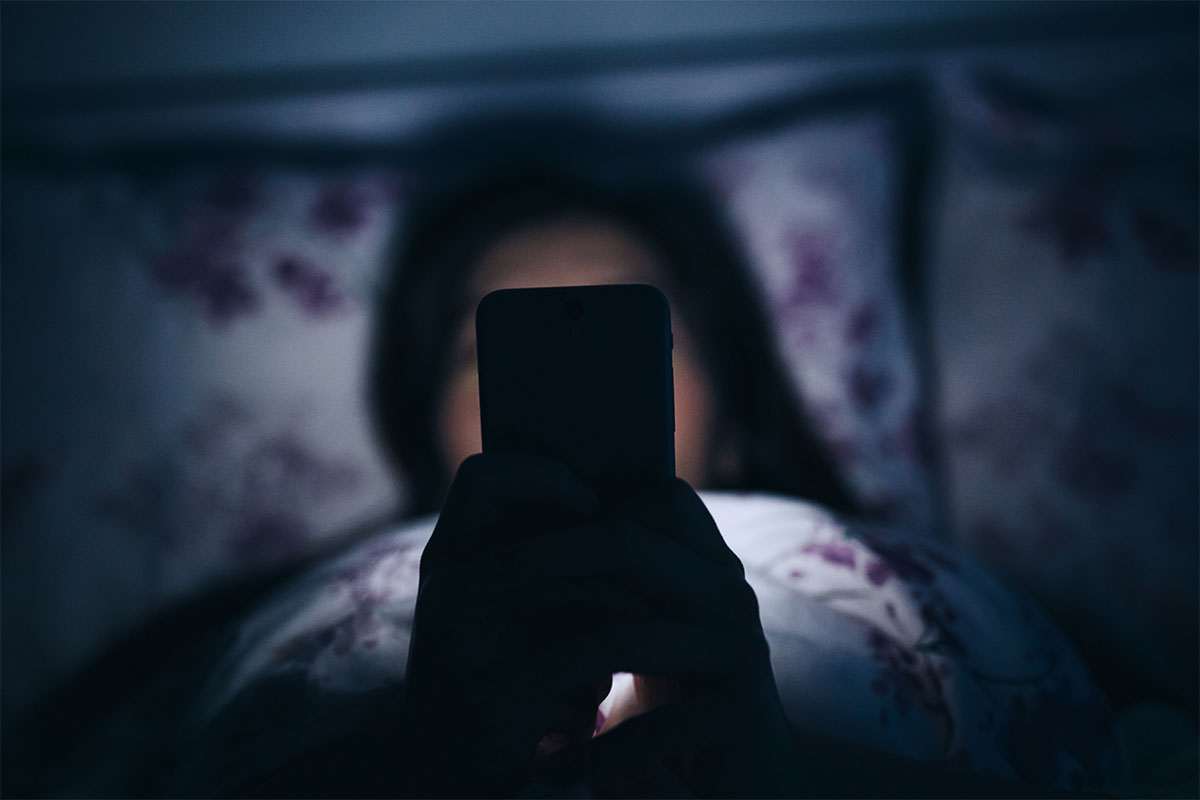 """A woman in bed at night with her smartphone. New research suggests """"night modes"""" on phones don't really help with sleep."""