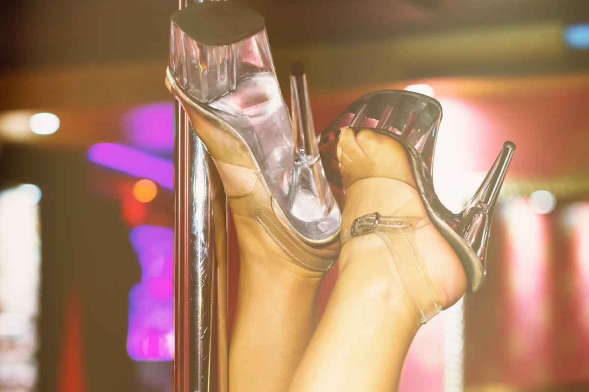 A woman's feet wearing heels wrapped around a stripper pole