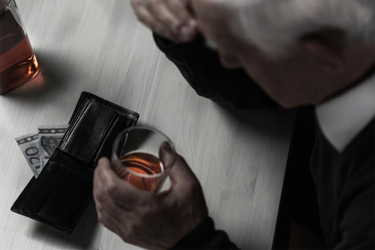 a man drinking whiskey with his wallet open