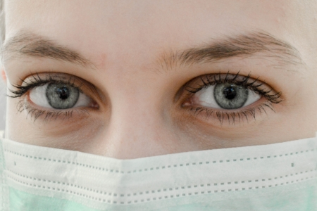 A closeup photo of a woman's eyes over her face mask