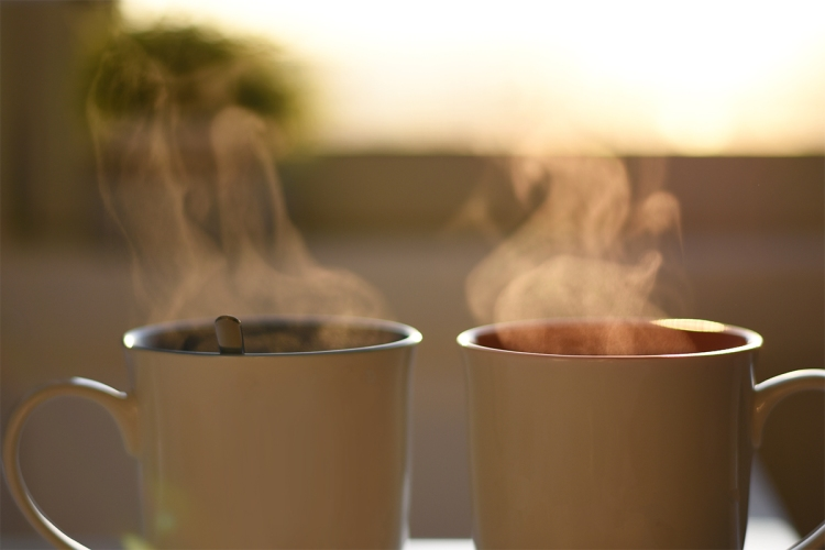 Steam rising off of two cups of coffee with the sunrise in the background