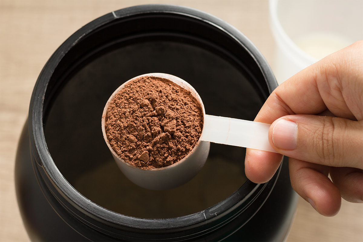 A scoop of brown pre-workout powder