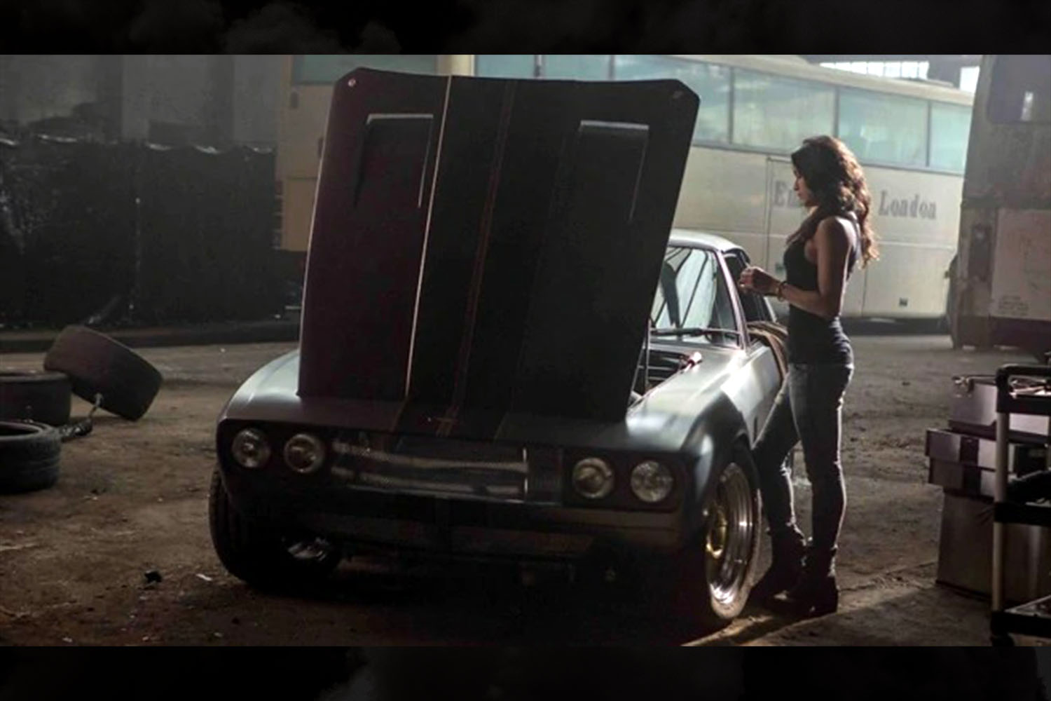 Letty Ortiz (Michelle Rodriguez) standing over a 1971 Jensen Interceptor in a garage in a scene from Fast & Furious 6