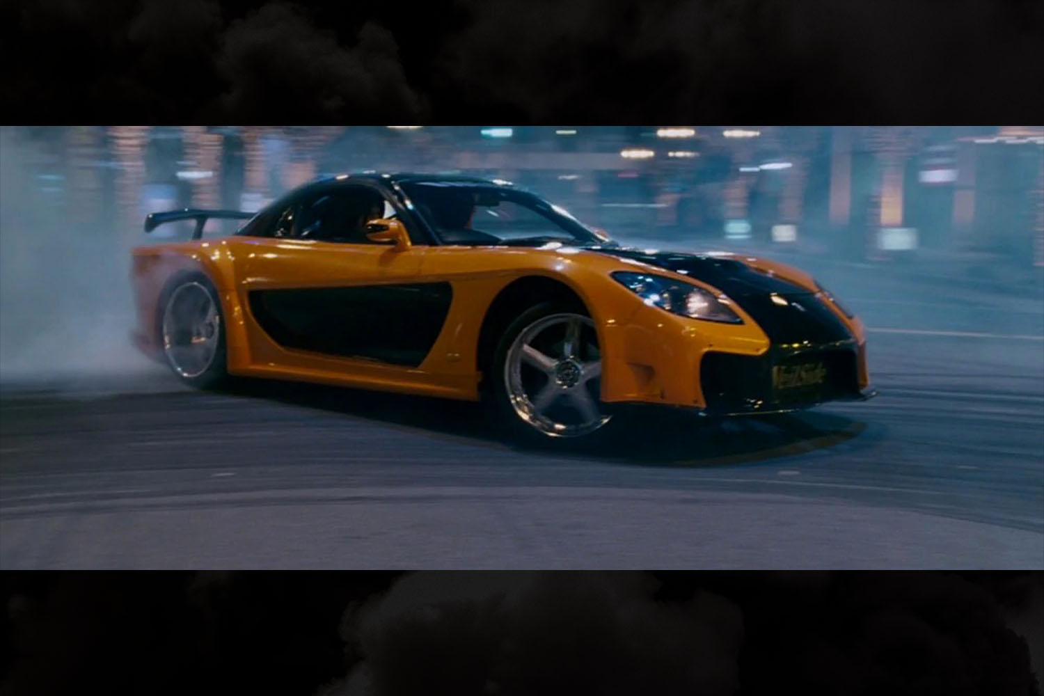 The orange and black 1997 Mazda RX-7 Veilside driven by Han in The Fast and the Furious: Tokyo Drift