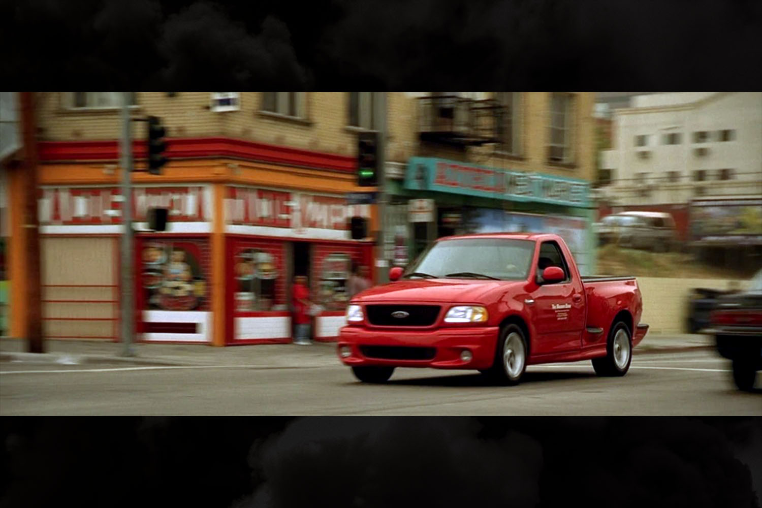 A red Ford F-150 SVT Lightning pickup truck in a scene from the original Fast and Furious movie