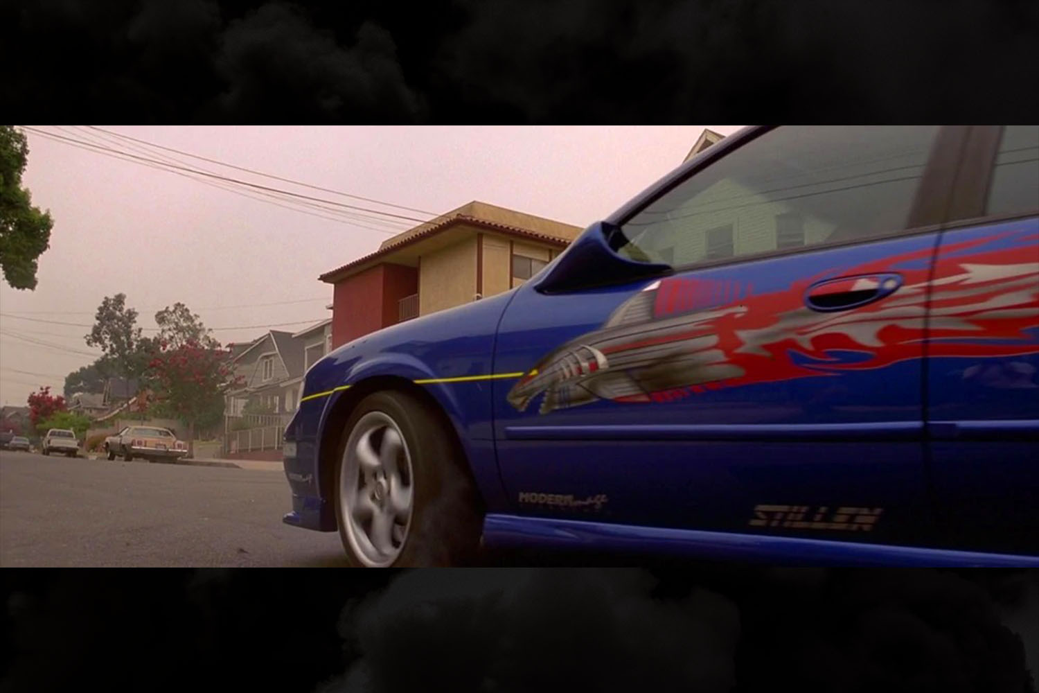 The shark torpedo graphics on the side of Vince's blue 1999 Nissan Maxima in the original The Fast and the Furious