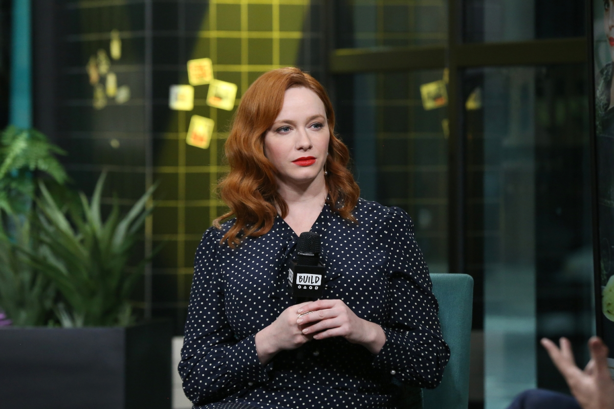 Christina Hendricks holds a microphone on stage, unsmiling