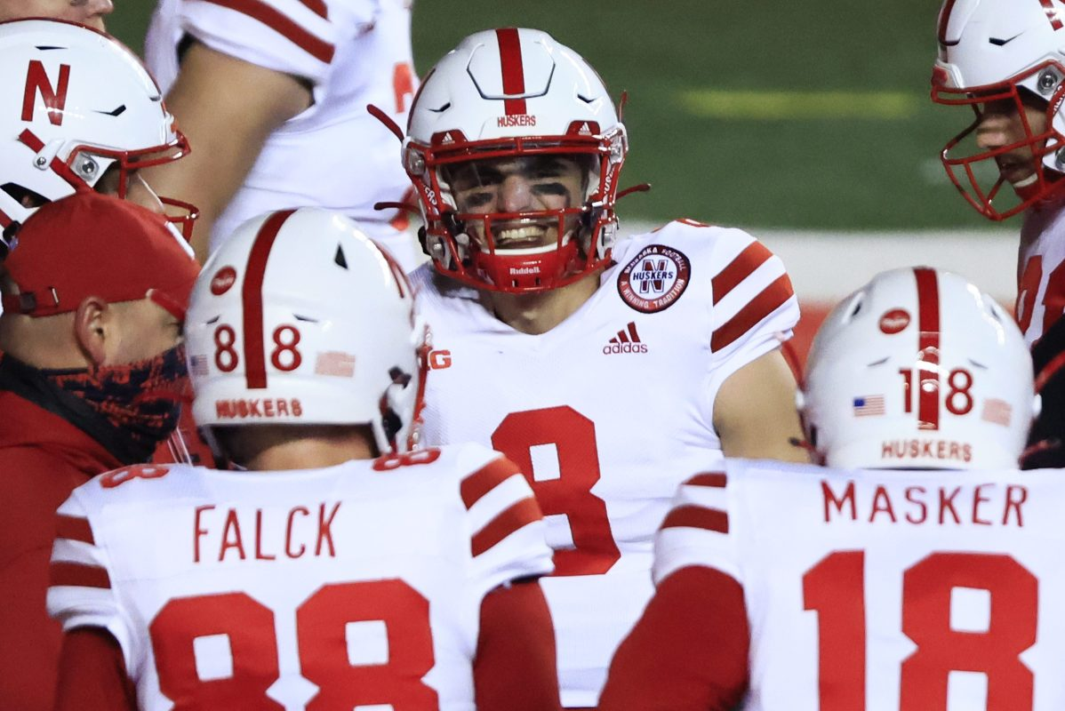 Nebraska Cornhuskers football players in red and white uniforms on the field. The school will soon help the players cash in on their name, image and likeness.