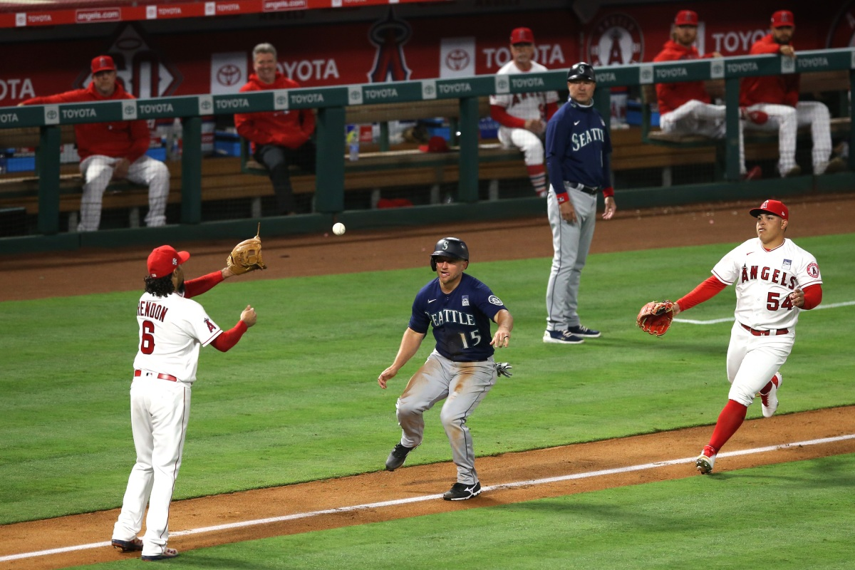 ANAHEIM, CALIFORNIA - JUNE 03: Kyle Seager #15 of the Seattle Mariners is caught in a rundown between Anthony Rendon #6 and Jose Suarez #54 of the Los Angeles Angels after stealing third base in the fifth inning at Angel Stadium of Anaheim on June 03, 2021 in Anaheim, California.