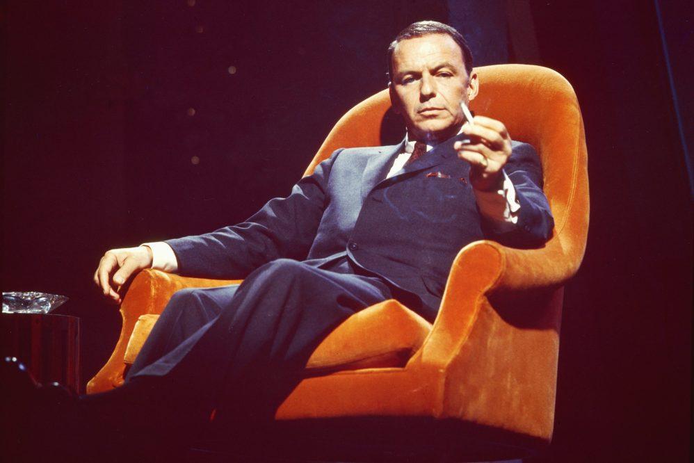 Frank Sinatra sitting in an orange chair in 1955