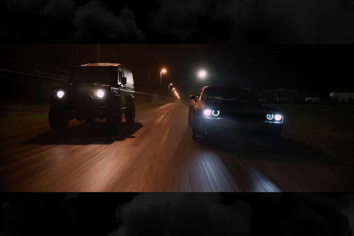 """Luke Hobbs played by Dwayne """"The Rock"""" Johnson driving a Land Rover Defender at night in a scene from The Fate of the Furious"""