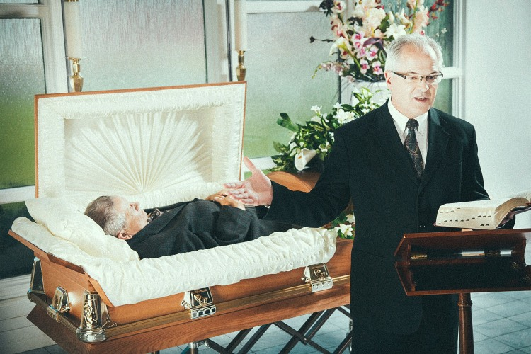 An older man giving a eulogy for another man (deceased) behind him in a coffin