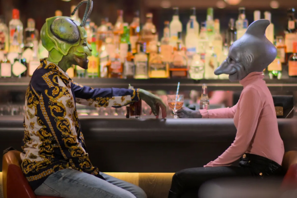 """A woman wearing a dolphin head and a man wearing a bug head sit at a bar in the trailer for Netflix's """"Sexy Beasts."""""""