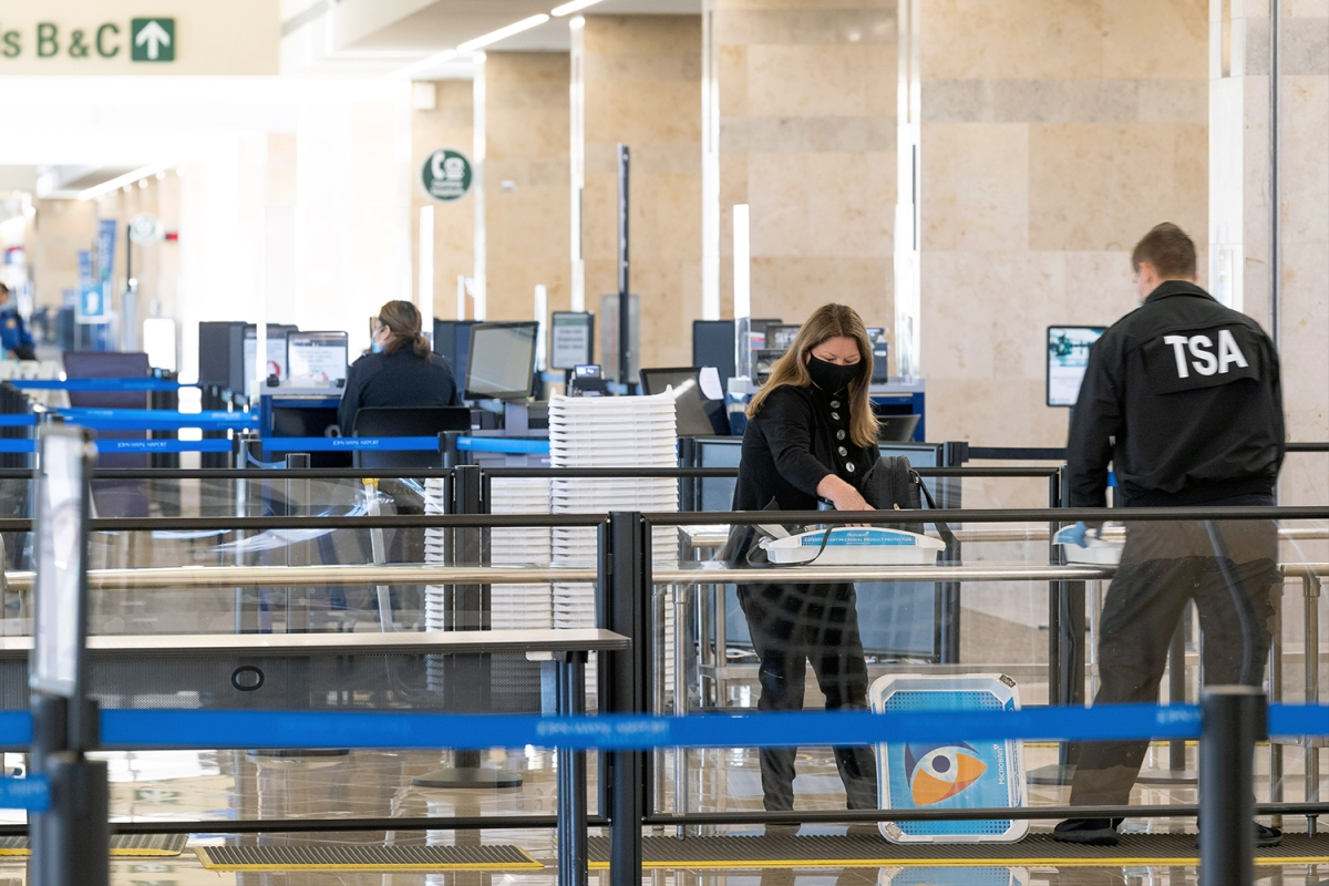 A TSA agent helps a traveler through security checkpoint at John Wayne Airport