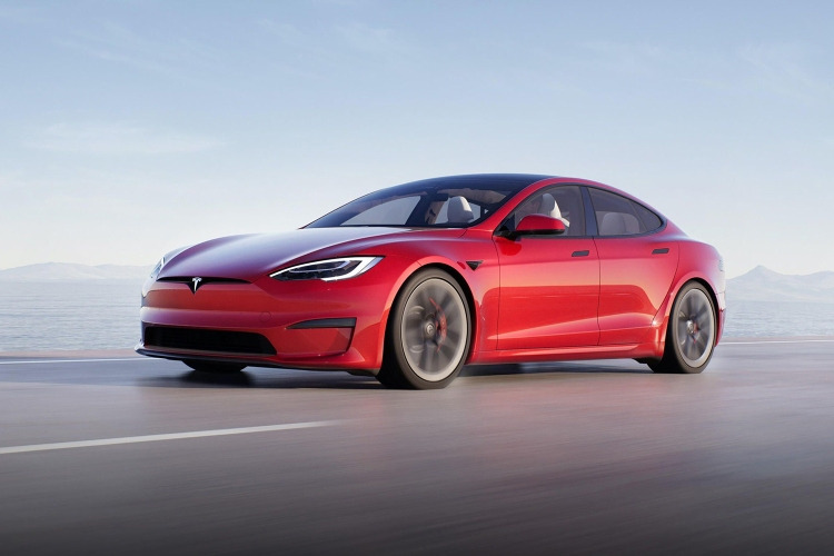 A red Tesla Model S Plaid driving down the road
