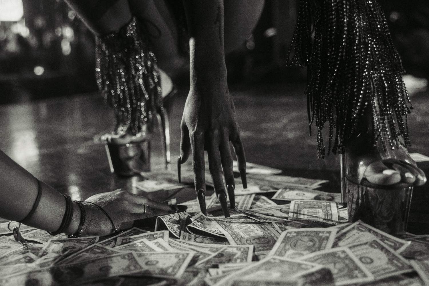 Black and white photo shows a stripper's hand touching the floor, covered in dollar bills