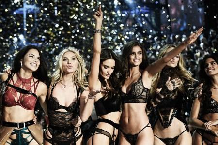 Victoria's Secret Angels pose on stage against sparkling background