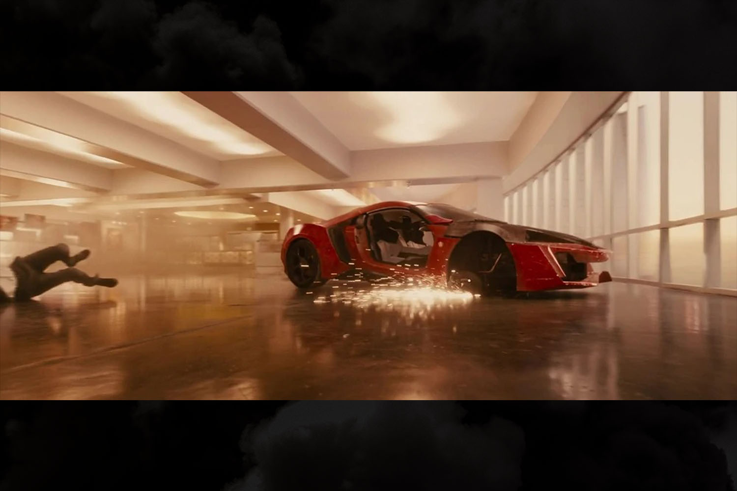 """The red W Motors Lykan HyperSport getting wrecked as Dom and Brian jump it through skyscrapers in the movie """"Furious 7"""""""