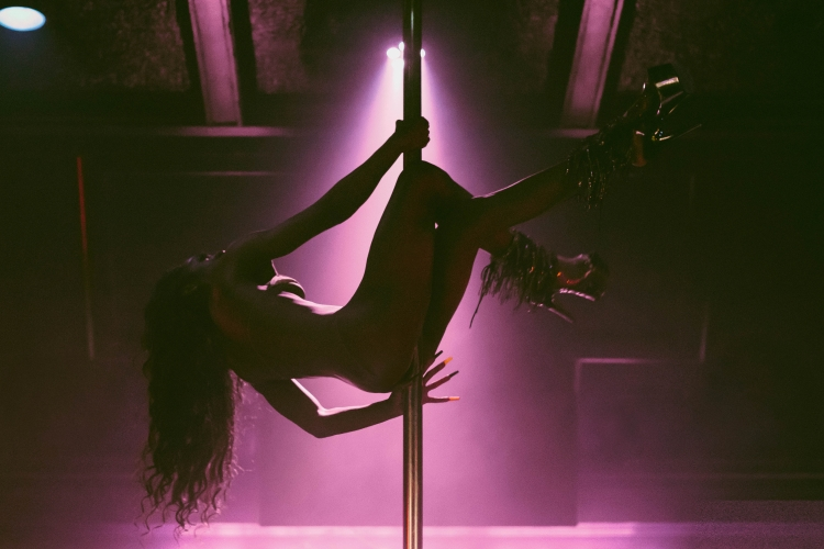 A dancer hanging from a stripper pole against purple stage lights