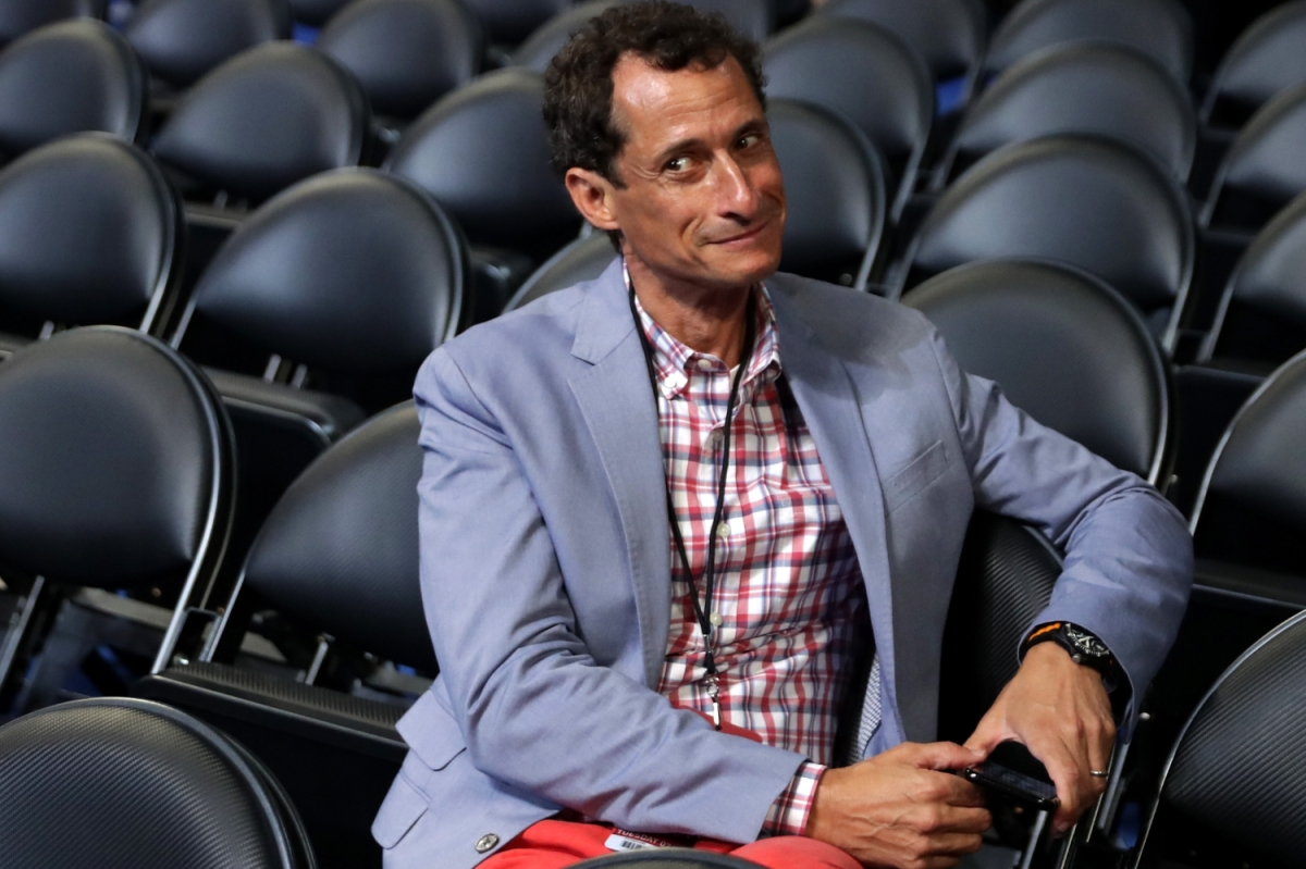 anthony weiner sitting in rows of black folding chairs holding phone