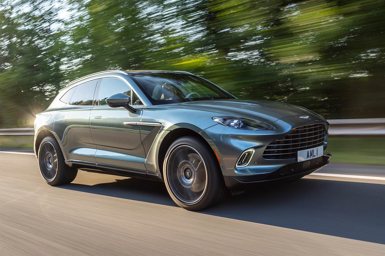 2021 Aston Martin DBX in green driving down the road