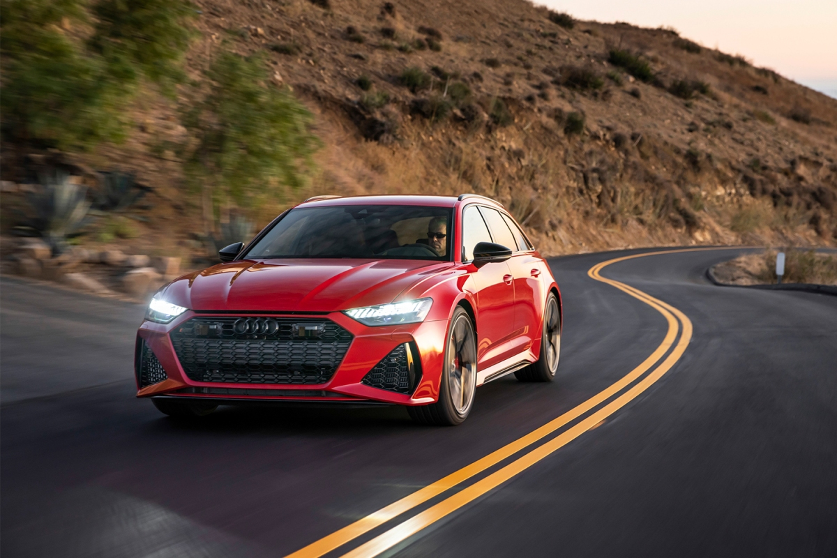 A red 2021 Audi RS 6 Avant driving down a coastal highway. We took the high-powered station wagon for a test drive.