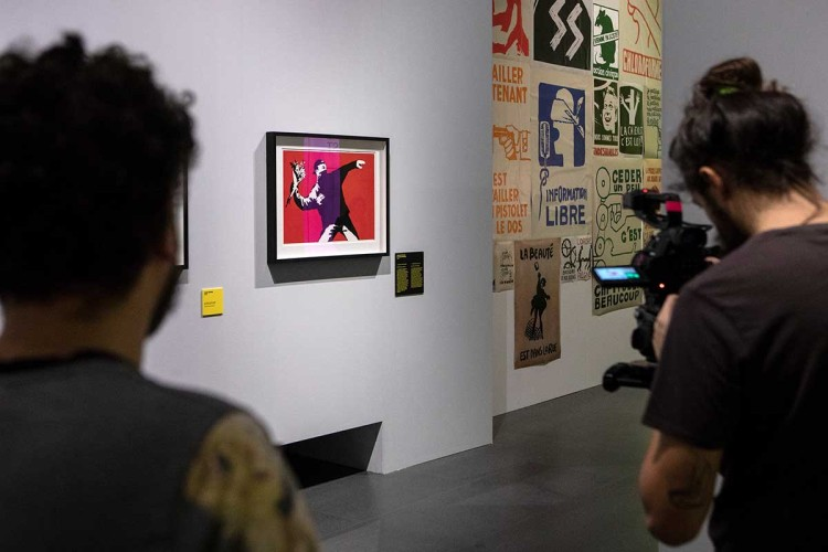 """A video maker films Banksy's work """"Love is in the Air (Flower Thrower)"""" during the press preview of the """"The Art of BANKSY. A Visual Protest"""" exhibition at MUDEC on November 20, 2018 in Milan, Italy."""