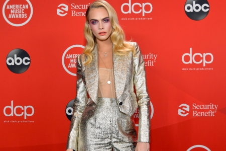 Model Cara Delevingne showed off her home in a recent appearance. The image shows the star posing in a silver pantsuit against a red backdrop.