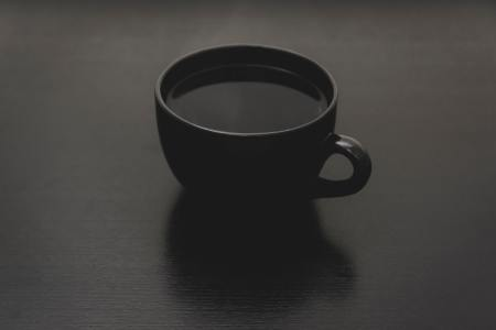 A cup of black coffee in a black mug on a black table