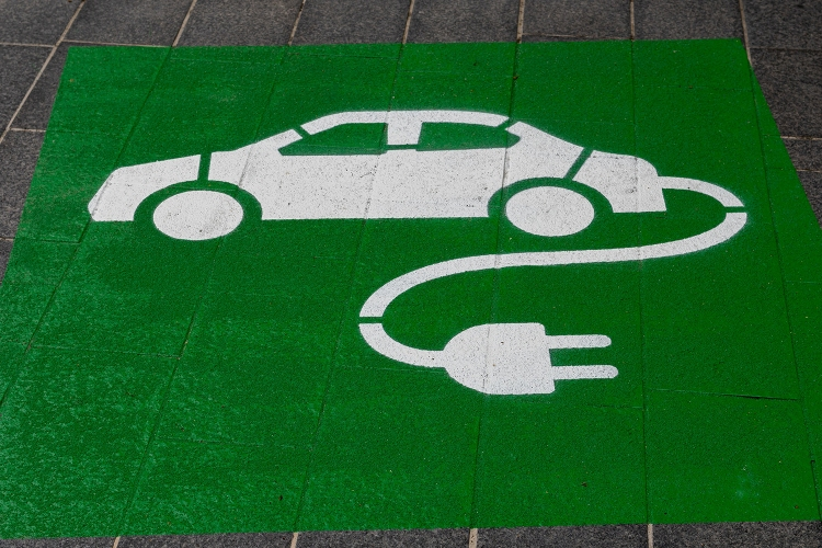 A green and white electric car symbol on a parking space